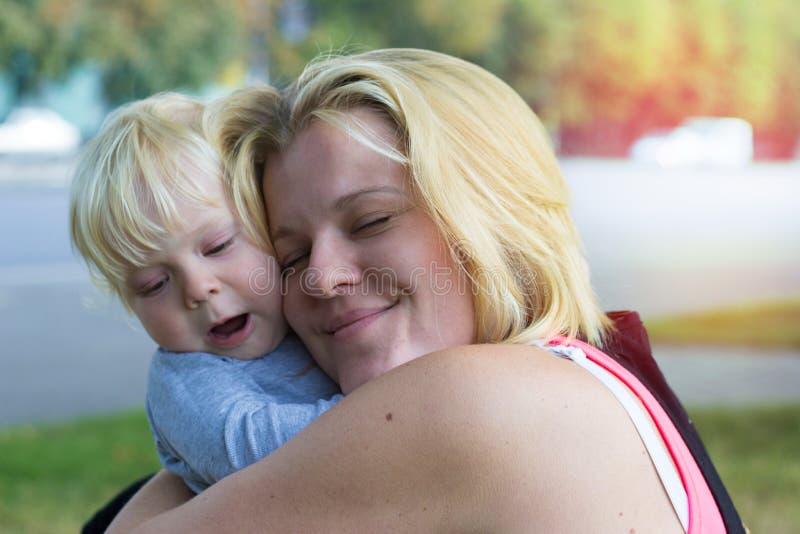 Mime a abrazar a su hijo, estropeado la los ojos en placer imagen de archivo libre de regalías