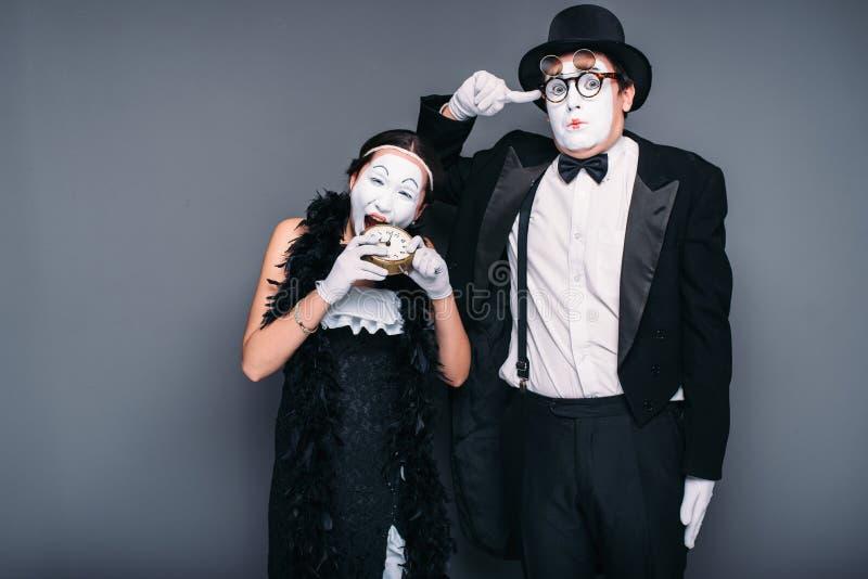 Mime actors performing, actress nibble alarm clock. Pantomime theater performers stock photos