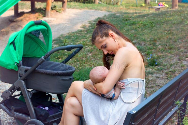 Mime al bebé que cuida en los brazos cariñosos, amamantando al bebé en público, mamá bonita está llevando el vestido del verano q foto de archivo