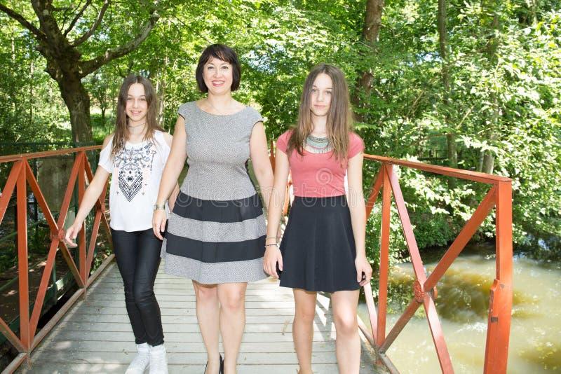 Mime al paseo en el puente del parque con la hija de dos gemelos imagen de archivo libre de regalías