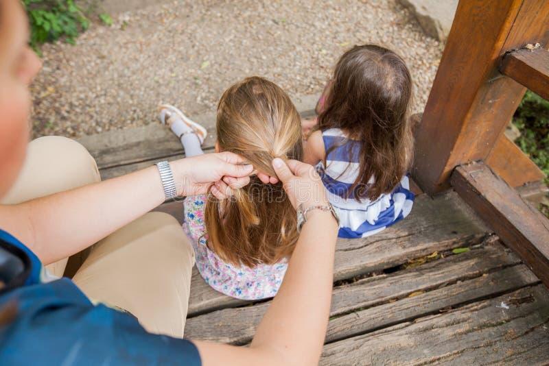Mime al pelo del ` s de la hija que se peina y que trenza imagen de archivo