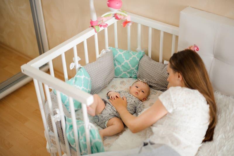 Mime al pequeño bebé recién nacido lindo que se calma en cama fotografía de archivo libre de regalías