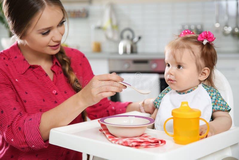 Mime a alimentar a su pequeño bebé con la comida sana imagen de archivo