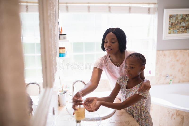 Mime a ayudar a la hija mientras que lava las manos en cuarto de baño imagen de archivo libre de regalías