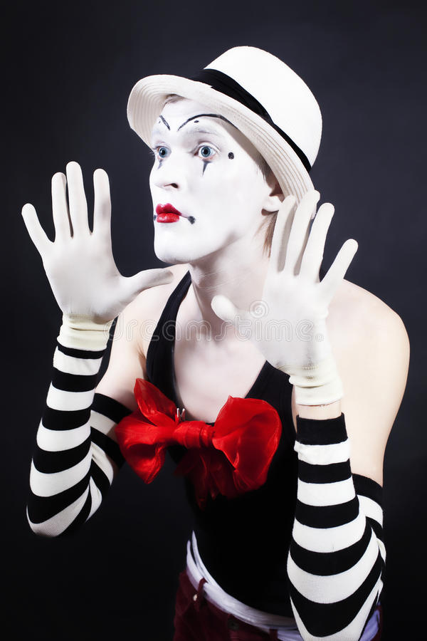 Mime con il cappello bianco di ina rosso dell'arco ed i guanti a strisce fotografia stock libera da diritti