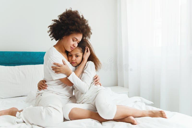 Mime a confortar a su hija, sentándose en el dormitorio foto de archivo