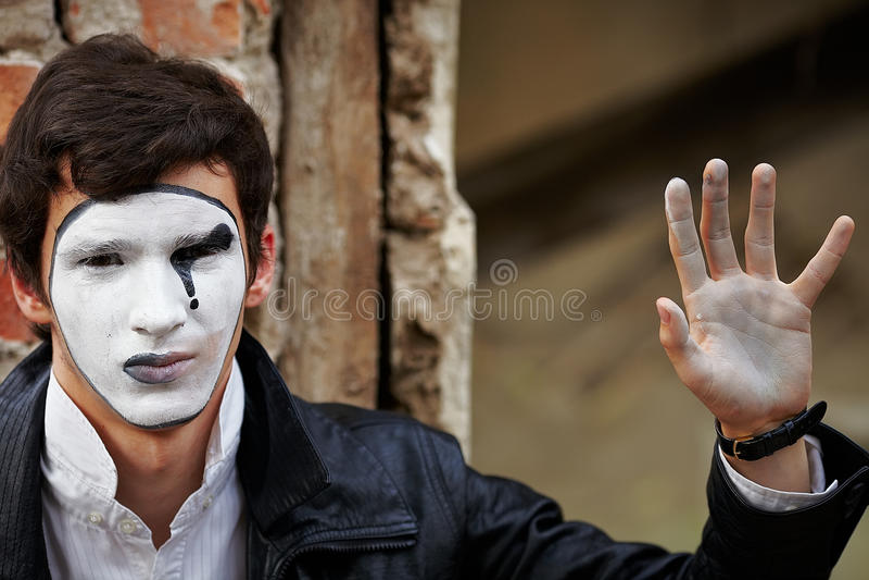 Mime del individuo contra una pared de ladrillo vieja. imagenes de archivo