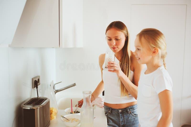 Mime a desayunar con la hija del niño en casa en cocina blanca moderna imagenes de archivo