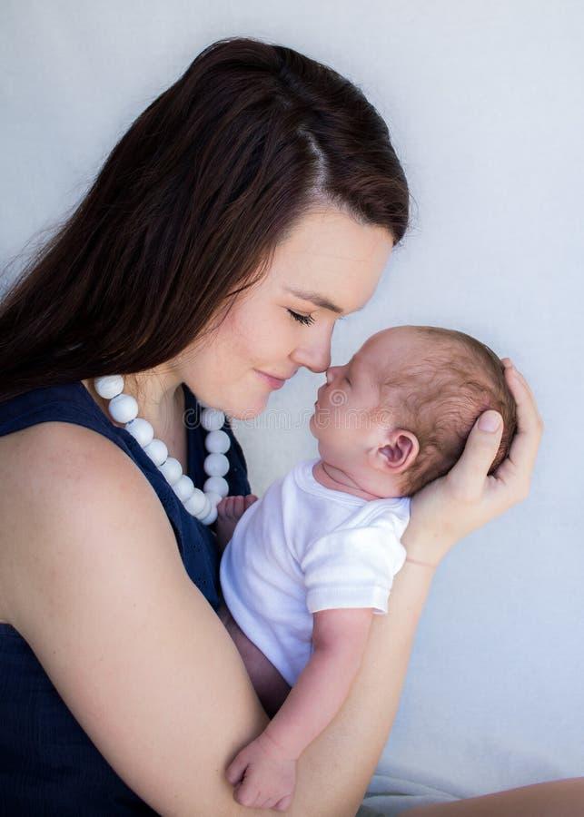 Mime a detener al bebé recién nacido durmiente que toca sus narices juntas imagenes de archivo
