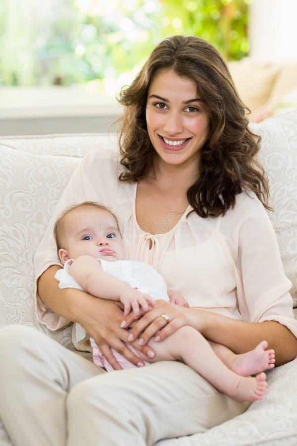 Mime a detener a su bebé en revestimiento en sala de estar foto de archivo