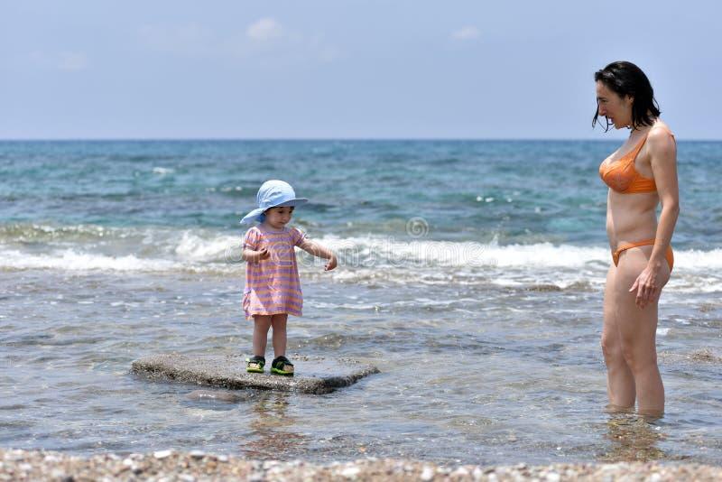 Mime a divertirse con su bebé del niño en agua de mar imagenes de archivo