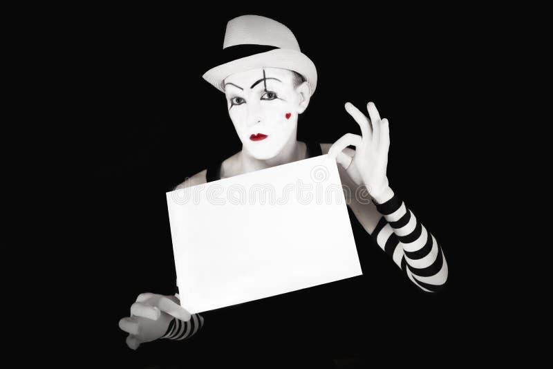 Mime en los guantes rayados que llevan a cabo el espacio en blanco blanco imagen de archivo