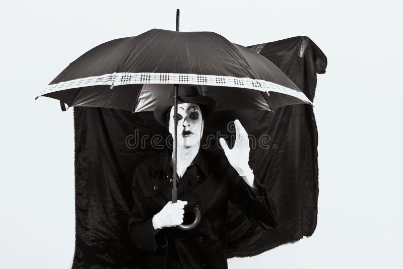 Mime en un sombrero que sostiene un paraguas en su mano imágenes de archivo libres de regalías