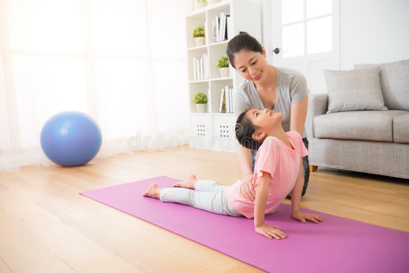 Mime a enseñar a su pequeña muchacha sus nociones de la yoga foto de archivo
