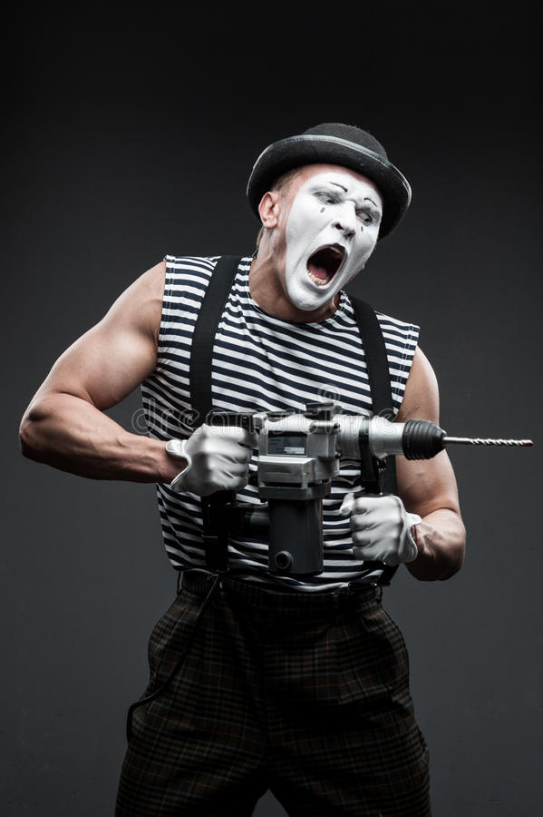Mime with hammer drill. Finny agressive mime holding puncher stock images
