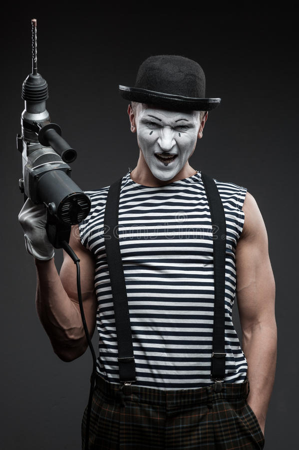 Mime with hammer drill. Funny aggressive mime holding puncher stock photo