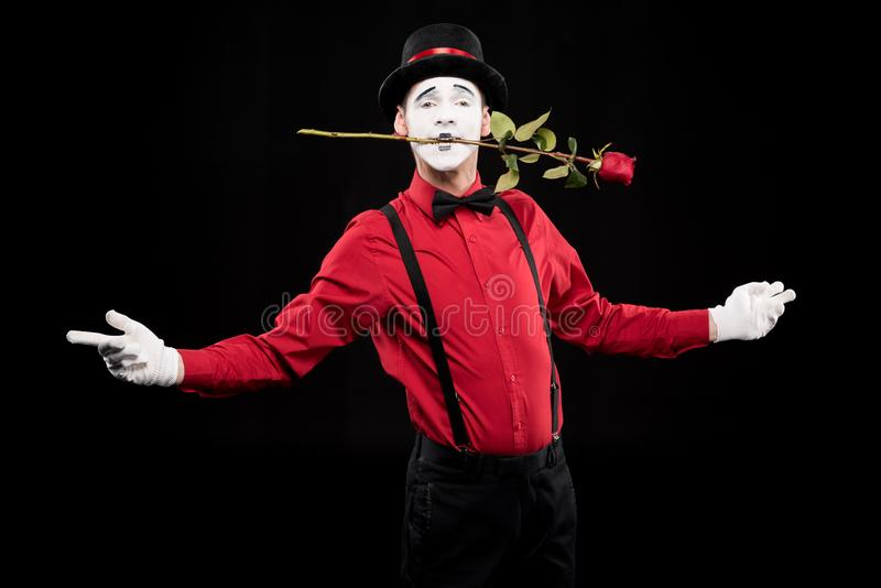 mime holding red rose in mouth and standing with open arms stock photo