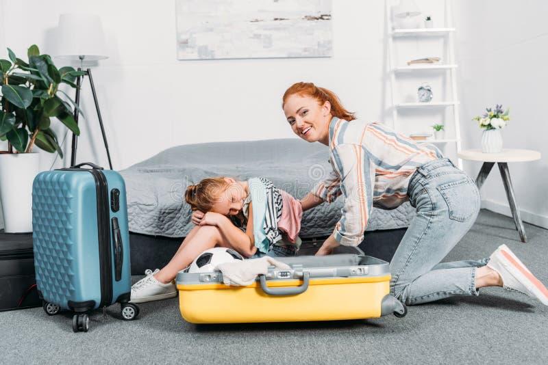 mime a intentar embalar la ropa en la maleta mientras que sentada adorable de la hija foto de archivo