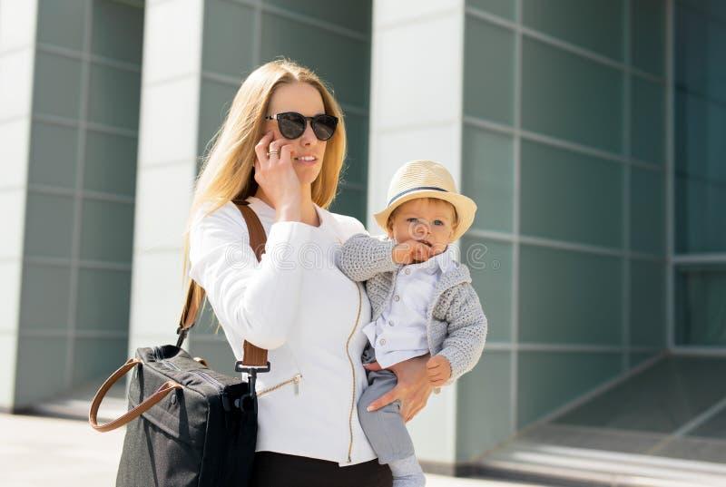 Mime a ir a trabajar y a hablar en el teléfono con el bebé en sus manos imagen de archivo