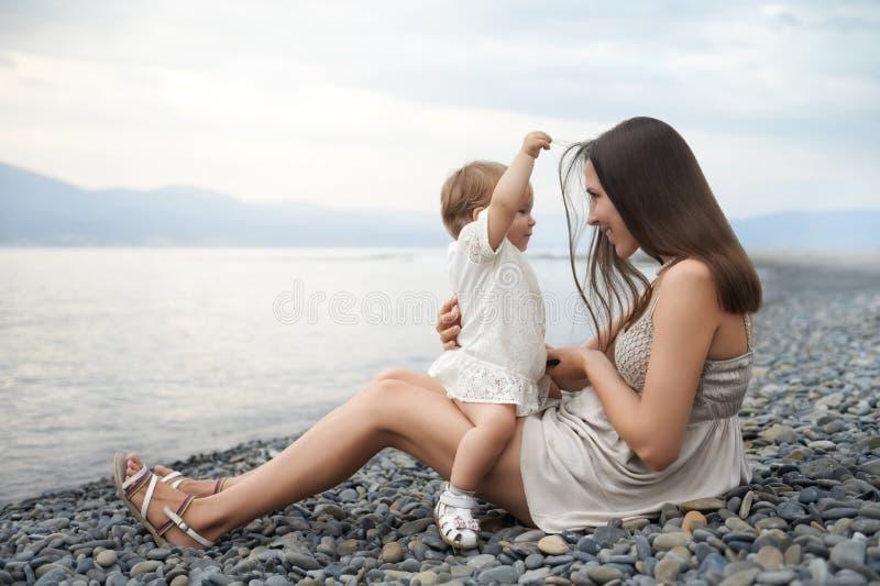 Mime a jugar con su hija en la playa imagenes de archivo