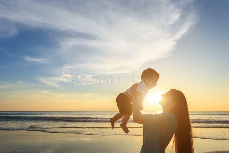 Mime a jugar con su hijo en la playa en el tiempo de la puesta del sol out fotos de archivo