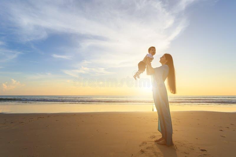 Mime a jugar con su hijo en la playa en el tiempo de la puesta del sol out fotografía de archivo