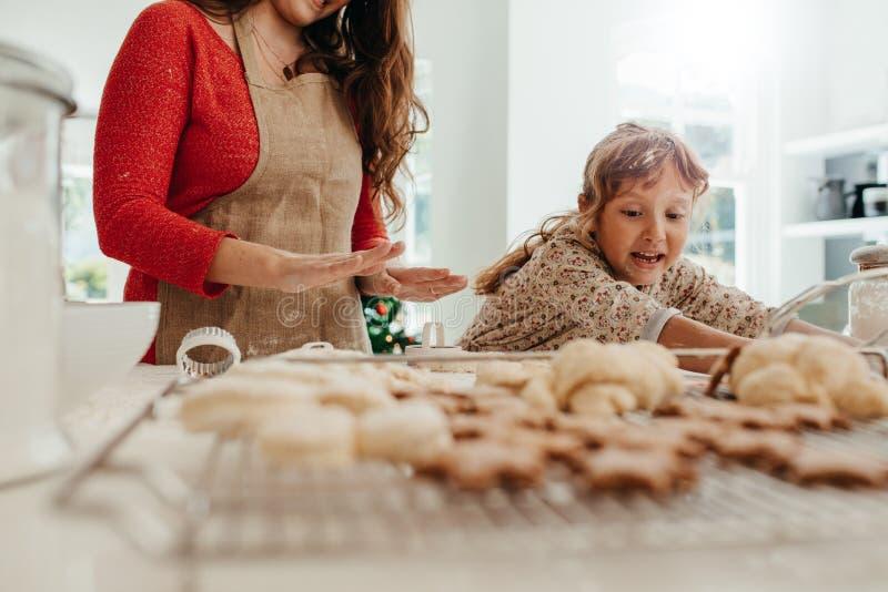 Mime a la hija de enseñanza para hacer las galletas para la Navidad imagen de archivo