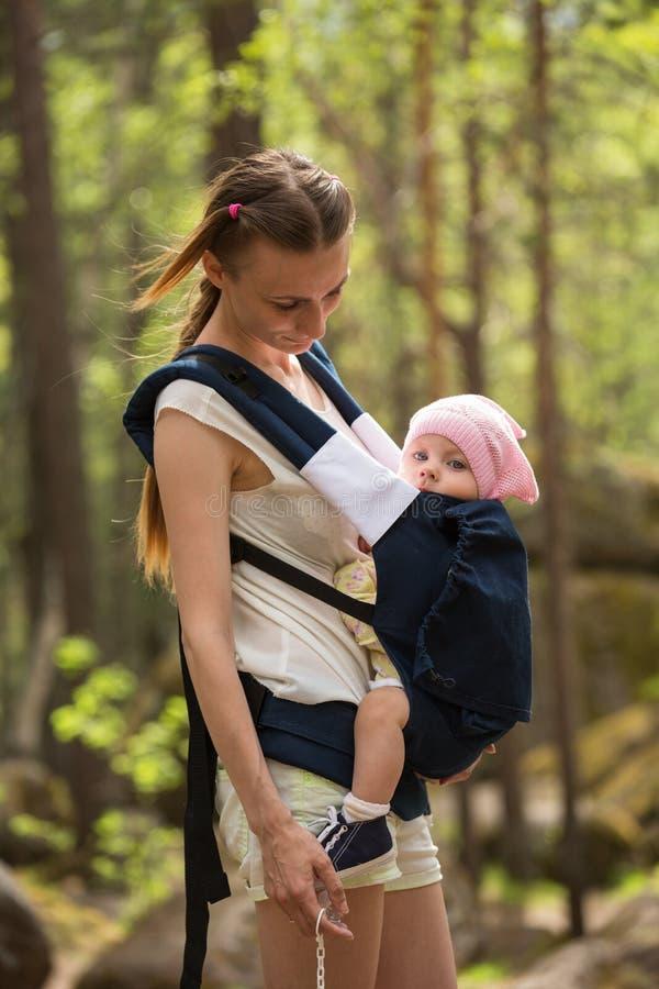 Mime a la hija que lleva en honda en un bosque imágenes de archivo libres de regalías