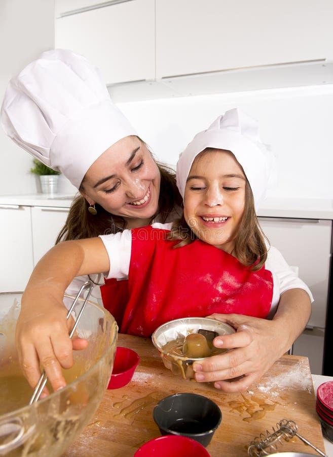 Mime a la hornada con la pequeña hija en delantal y cocine los molletes del molde del relleno del sombrero con pasta del chocolat fotografía de archivo libre de regalías
