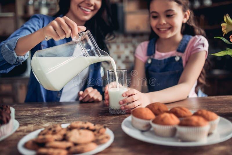 Mime a la leche de colada en el vidrio para la hija fotos de archivo