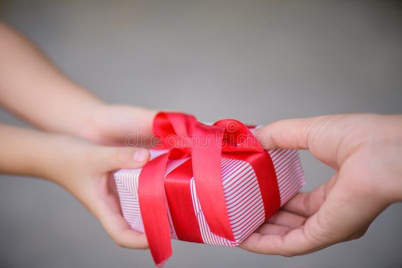 Mime a la mano que da una caja de regalo a su niño Días de fiesta, presente, imagen de archivo libre de regalías