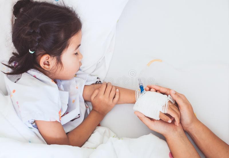 Mime a la mano que lleva a cabo la mano enferma de la hija que tiene solución IV imagen de archivo libre de regalías