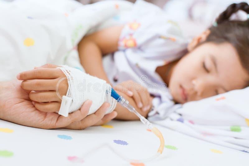 Mime a la mano que lleva a cabo la mano enferma de la hija que tiene solución IV foto de archivo libre de regalías