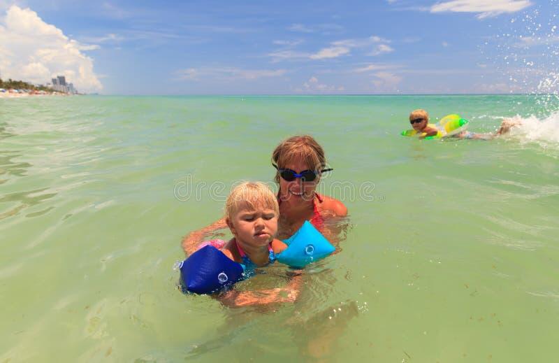 Mime a la pequeña hija de enseñanza para nadar en el mar fotografía de archivo