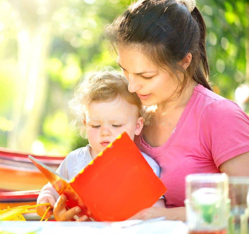 Mime a leer un libro a su pequeño bebé en parque soleado fotografía de archivo