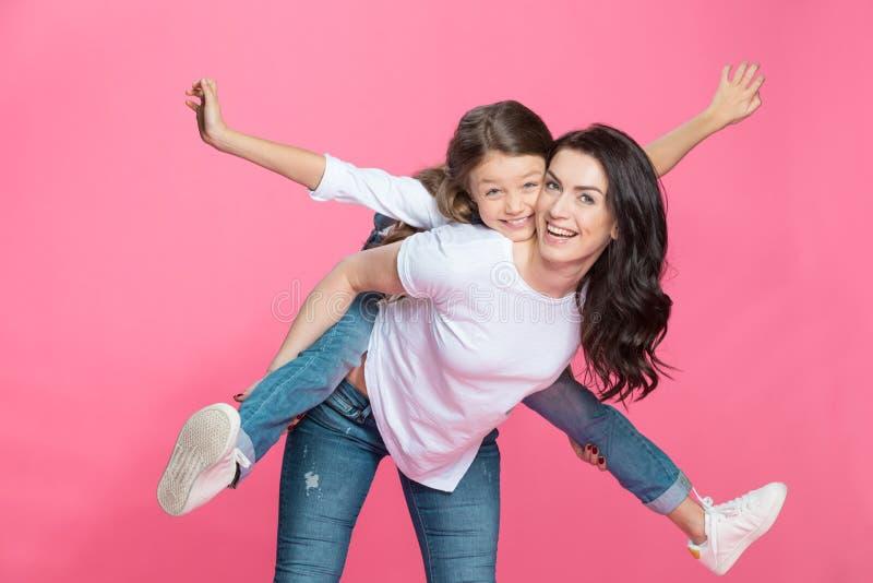 Mime a llevar a cuestas a la pequeña hija adorable que sonríe en la cámara fotos de archivo libres de regalías