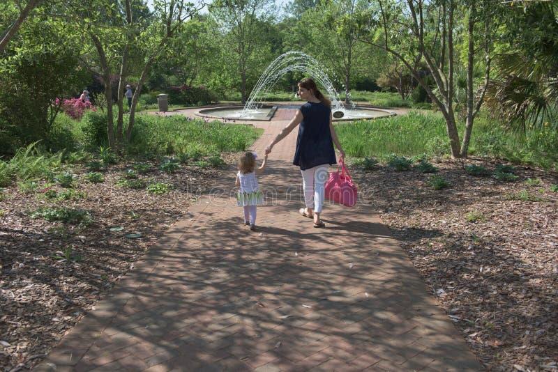 Mime a los controles su mano del ` s de la hija en un parque al aire libre foto de archivo libre de regalías