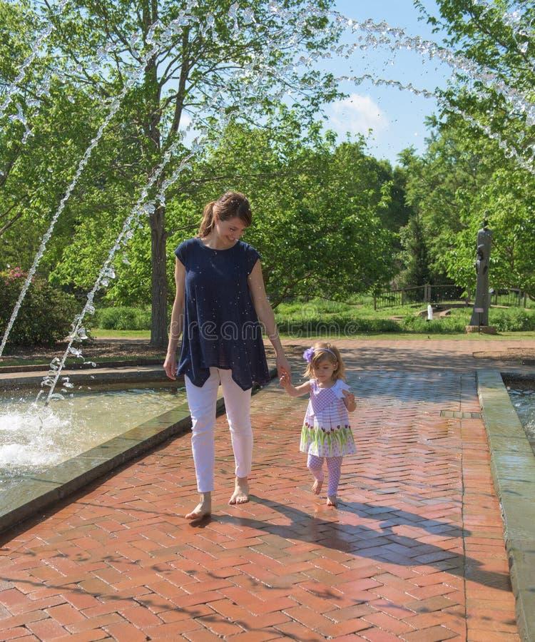 Mime a los controles su mano del ` s de la hija a través de una fuente de agua en un parque al aire libre fotos de archivo