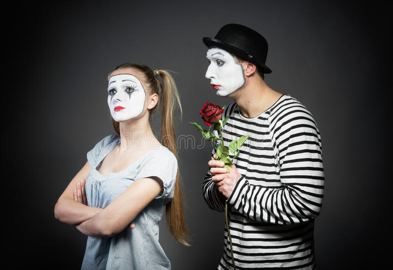 Mime in love. Male mime giving a flower to female mime royalty free stock photography