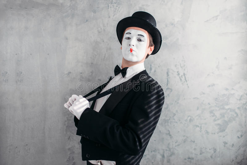 Mime male artist with white makeup mask. Comedy actor in suit, gloves and hat. Mimic person. April fools day concept stock photography
