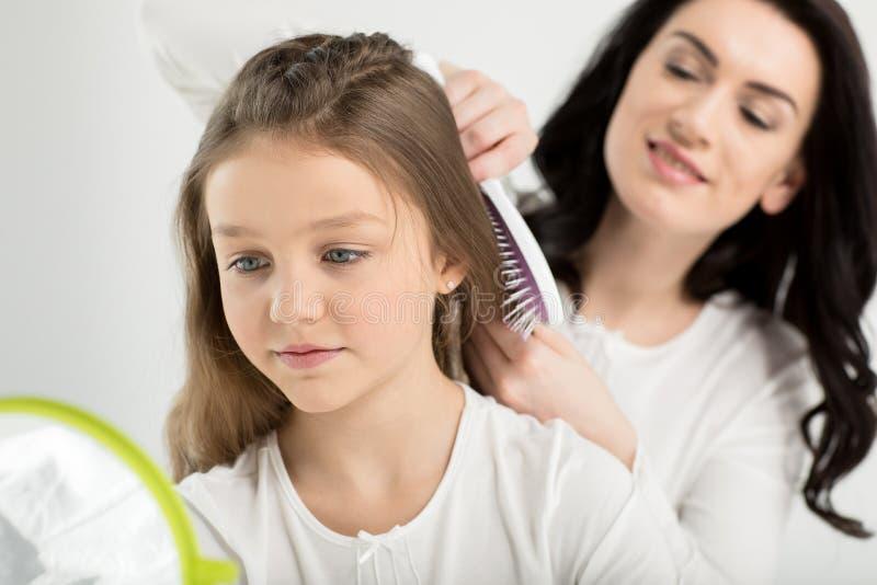 Mime a peinar el pelo de la pequeña hija linda que mira el espejo a mano foto de archivo libre de regalías