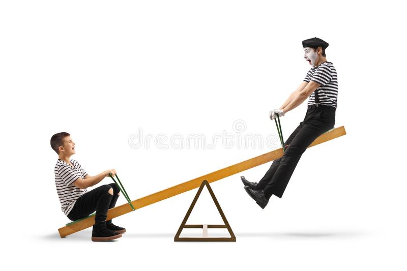 Mime playing on a seesaw with a teenage boy stock photo