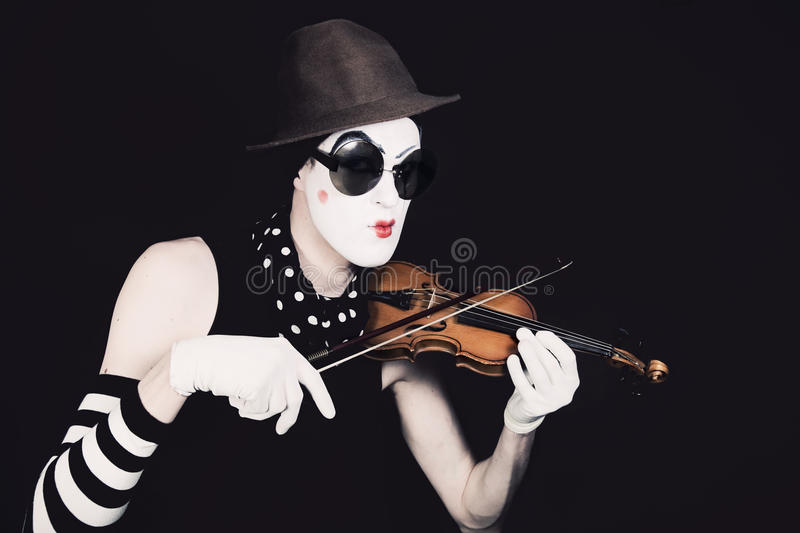 Mime playing on small violin in sunglasses stock photography