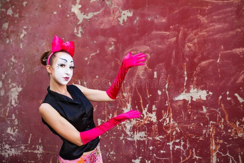 Mime points a finger at the center against a background of a red wall royalty free stock images