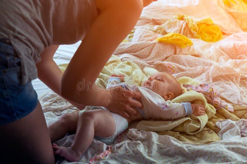 Mime pone los pañales y viste a un pequeño bebé foto de archivo libre de regalías