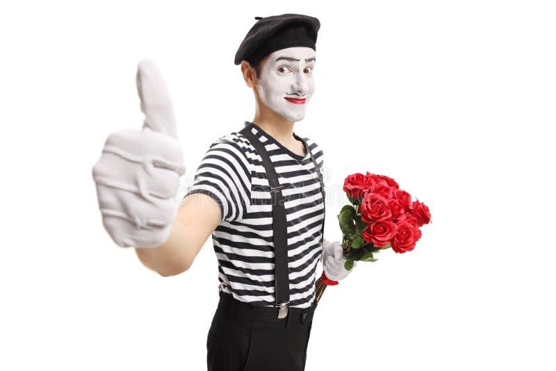 Mime que sostiene un manojo de rosas rojas que muestran los pulgares para arriba fotos de archivo libres de regalías