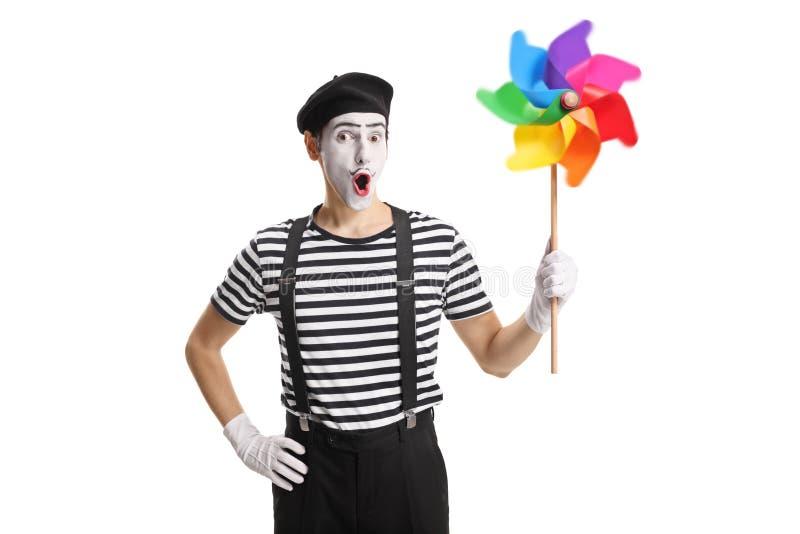 Mime que sostiene un molinillo de viento colorido de giro fotografía de archivo