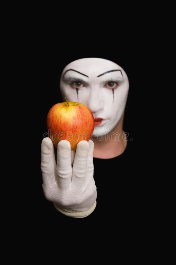 Mime with red apple. Portrait of Mime with red apple on black background stock image