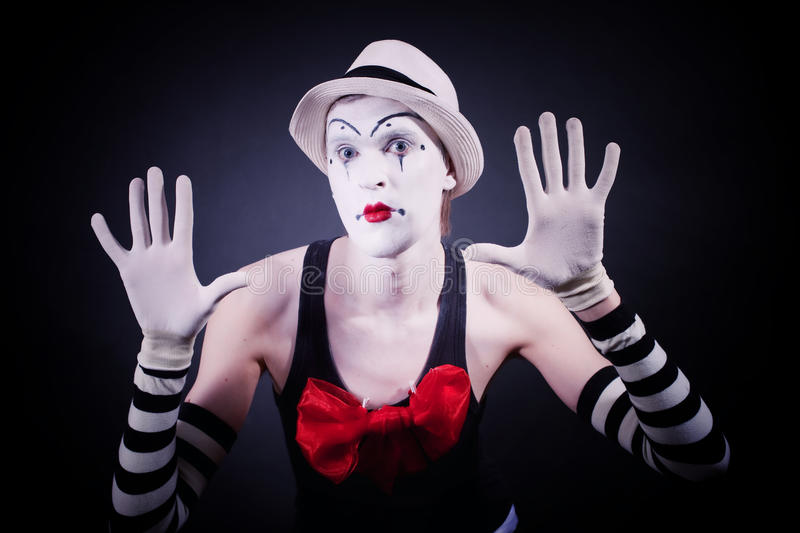 Mime with red bow. Funny Mime with red bow in a white hat and striped gloves on black background stock images
