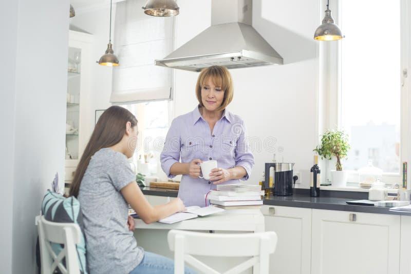 Mime a sostener la taza de café mientras que mira a la hija que estudia en cocina imagen de archivo